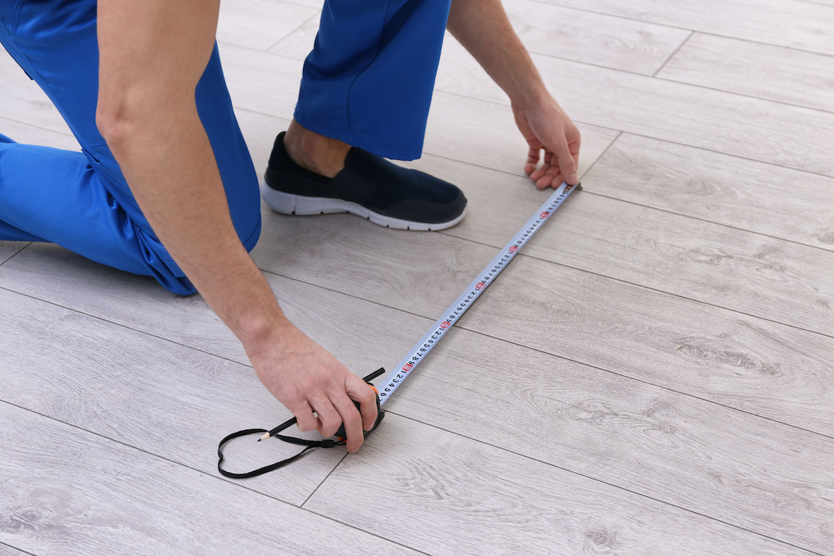man doing a home repair service by measuring the floor