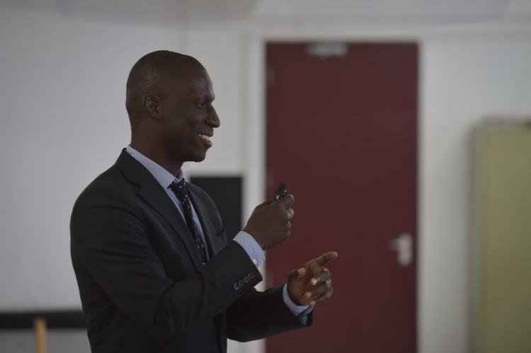 Un communicateur s'exprime durant une conférence en utilisant des gestes pour illustrer ses propos