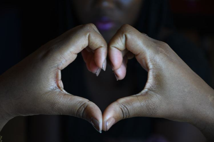 Une femme exprime son amour à travers un geste des deux mains