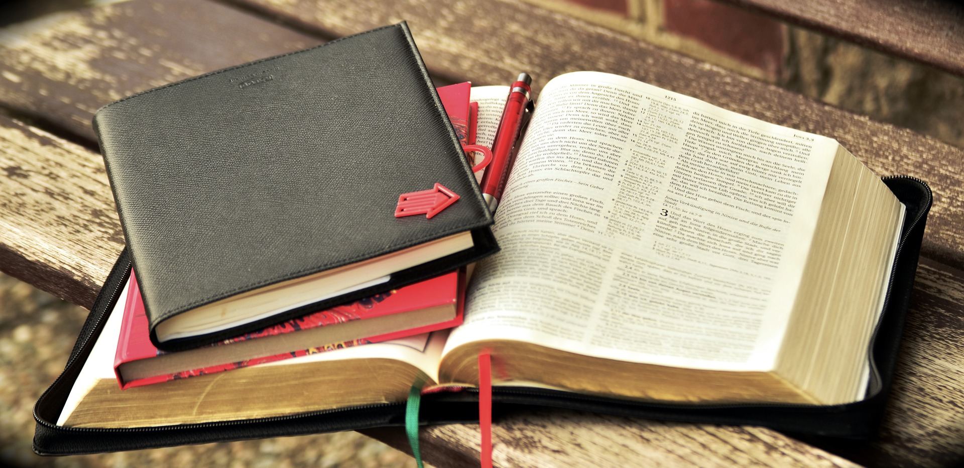 Open Bible with notebooks for study.