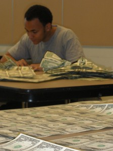 Sipho Mabona folding sheets of US dollar bills at JANM, March 2010