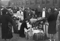 Japanese Americans near trains during Relocation.