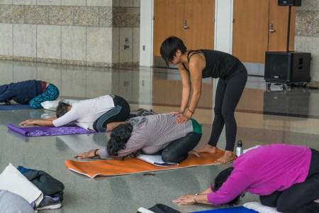 traci ishigo assists a yogi with a pose. Photo by Ben Furuta.