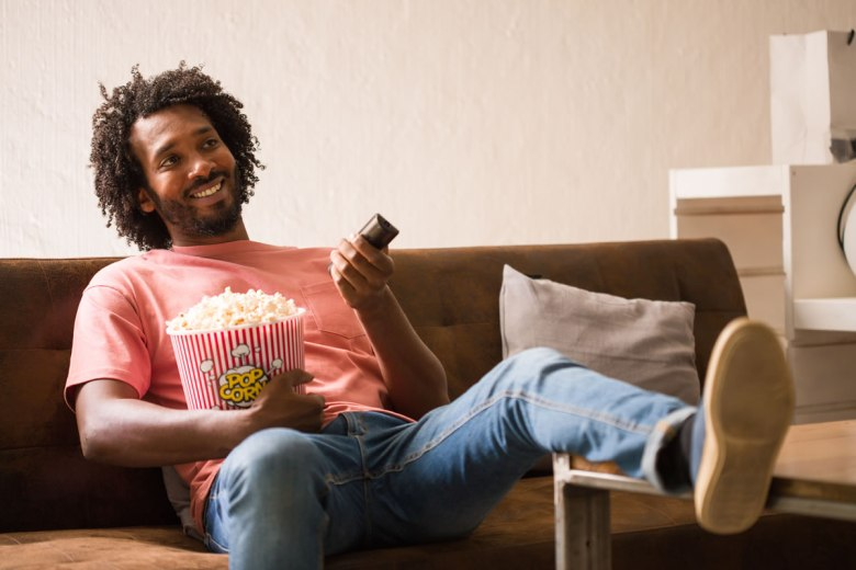 A man lounging in front of the TV with a bucket of popcorn and remote in hand