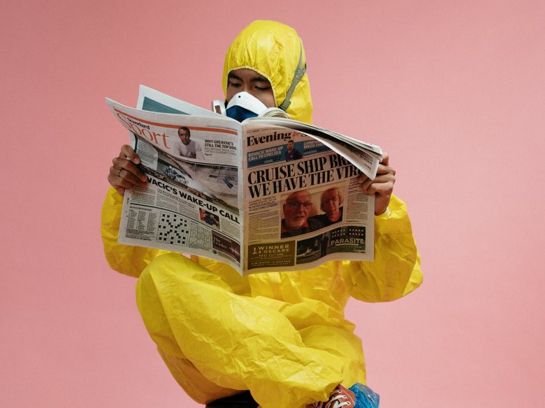 A man in a protective suit reading the newspaper