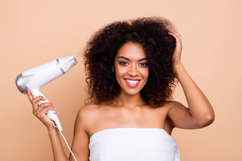 A woman blow drying her hair