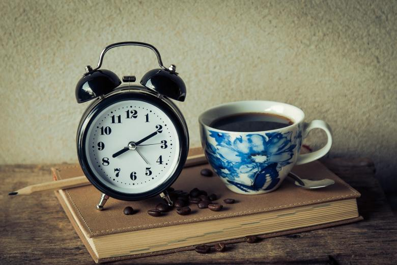An alarm clock and a cup of coffee