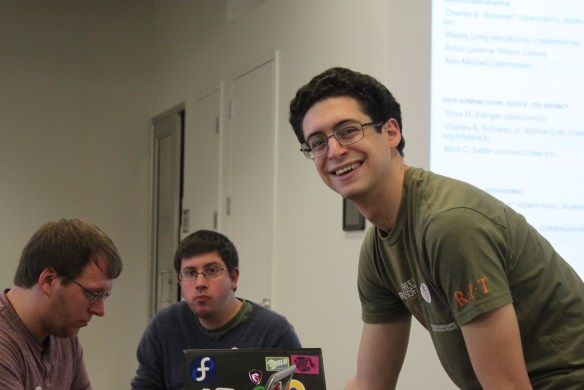 Dan Schneiderman updating the news sources on the projector screens during the Election Night Hackathon by FOSS at RIT