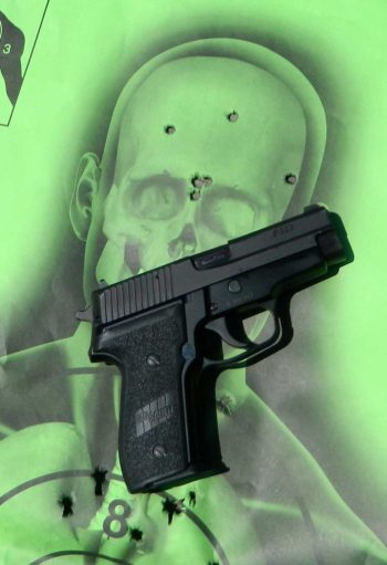 SIG Sauer P228 pistol on green skeleton target