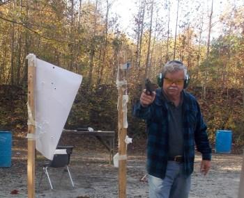Handgun pointed at the camera