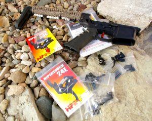 AR-15 on a bed of river rock with two Hipertouch triggers in the packaging