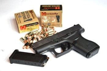 Glock G42 with two boxes of Hornady Critical Defense ammunition