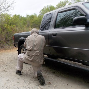 Bob Campbell crouching behind a pickup truck to provide cover and concealment