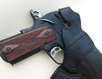 1911 pistol cocked and locked in a black leather holster