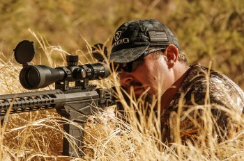 Hunter shooting an ar-15 for a hidden position in the tall grass