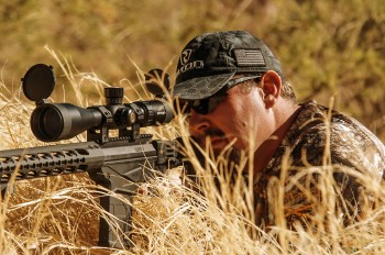 Hunter shooting an ar-15 for a hidden position in the tall grass
