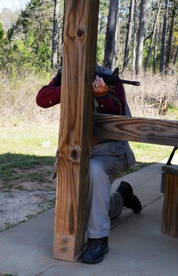 Man firing an AR-15 from behind a wood post