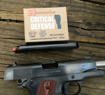 Colt 1911 with slide locked back and a box of Hornady Critical Defense ammunition
