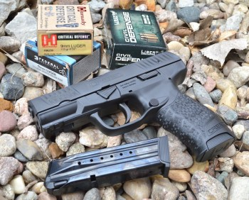 Walther Creed 9mm pistol left with spare magazine on bed of rocks