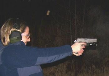 woman shooting a handgun at night