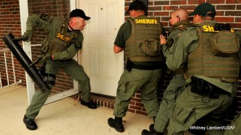 A Duplin County Sheriff's Office special response team member prepares to break down a door during a no-knock raid training exercise