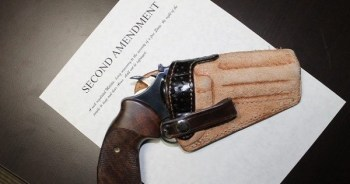 Revolver in leather holster on a copy of the Second Amendment for Gun Laws