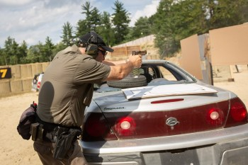 Man training to fire a pistol over the trunk of a car
