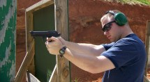 Man firing a pistol from a braced position