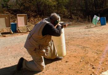 Bob Campbell firing a shotgun from behind a barrel barricade