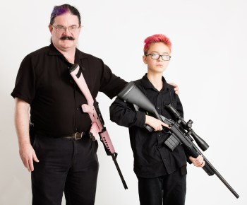 Father and son holding rifles at port arms