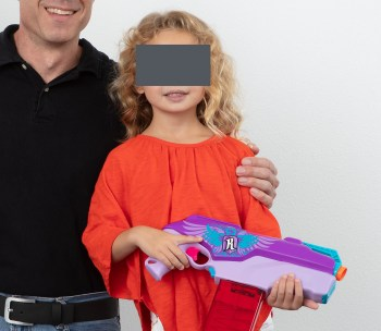 Father posing with daughter who is holding a toy dart gun