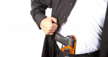 Man pulling back his suit jacket to reveal a gun in a holster