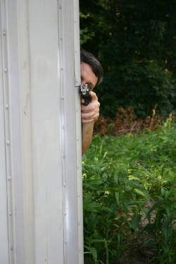 man shooting a pistol while using the corner of a metal shed as cover