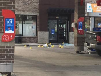 Broken glass and evidence markers at a gas station