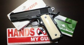 1911 handgun over several boxes of ammunition with gun control sticker