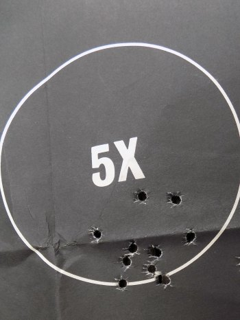 Silhouette target with multiple bullets holes in the 5 ring