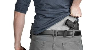 Man lifting his shirt to expose a concealed handgun