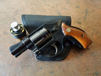 Smith and Wesson Model 40 revolver atop a black leather pocket holster
