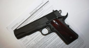 1911 pistol on a form 4473 NICS background check form for Cyber Monday