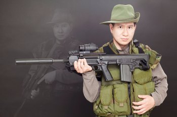 Asian man in battle dress holding an assault rifle, something that is not available in Hong Kong