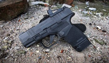 Springfield Hellcat pistol with red dot optic and industrial background in the dirt