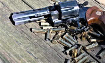 revolver laying atop a pile of spent shells