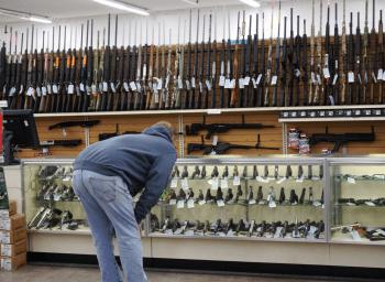 Man looking into glass counter display at handguns before his NICS check