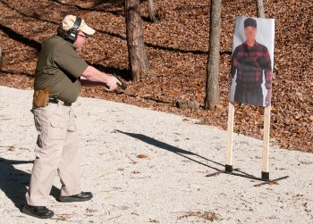 David Kenik inting a handgun at the ground in front of a target