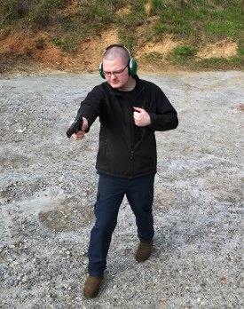 man moving while shooting a pistol for training