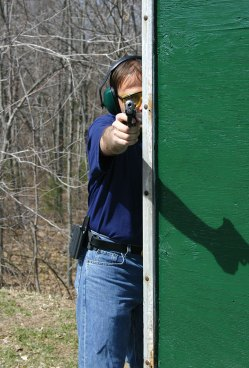 Man shooting a pistol with half of his body exposed and half behind cover