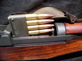 an en bloc clip being loaded into an M1 Garand rifle