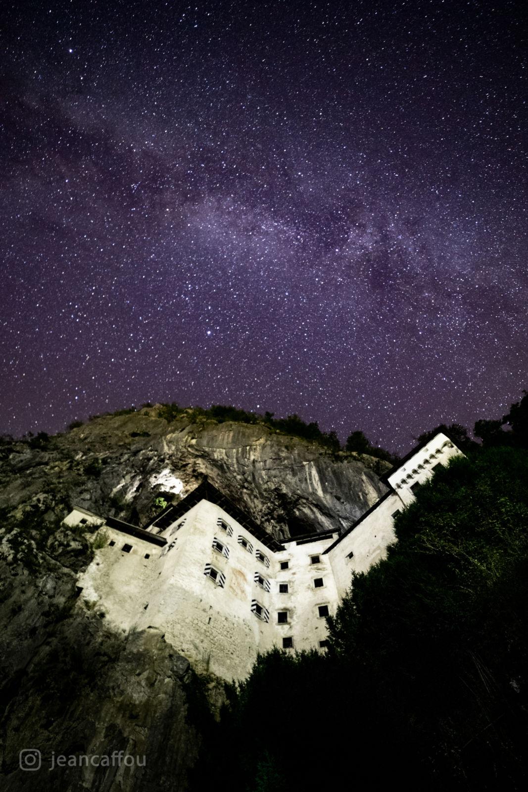 Predjamski grad ponoči z Rimsko cesto