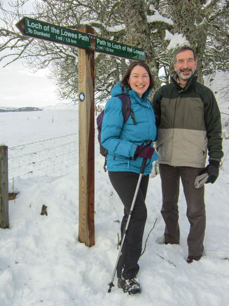 Father and daughter standing side by side in the snow in front of trees and a sign with directions to the Loch of the Lowes