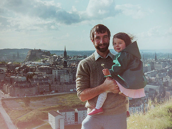 A young father holding his toddler-age daughter with the Edinburgh city skyline in the background